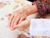 Jovem médico detém nas mãos da mulher idosa — Fotografia Stock