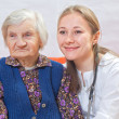 Old woman and the sweet young doctor staying together — Stock Photo