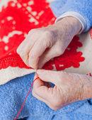 Old woman sews — Stock Photo
