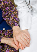 Elderly woman holds the doctor — Stock Photo