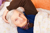 Elderly lonely woman rests in the bed — Stock Photo