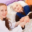 Young doctor holds the elderly woman hands — Stock Photo