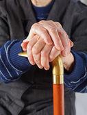 Elderly hands resting on stick — Stock Photo