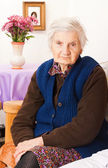 Elderly lonely woman sits on the bed — Stock Photo