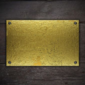 Gold metal plate on wooden background. Template for design — Stock Photo