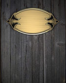 Beautiful pattern on a gold nameplate on a wood background — Стоковое фото