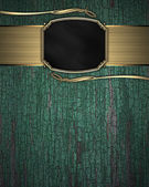 Gold Pattern on a black plate on a wood background — Stock Photo