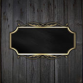 Beautiful pattern on a gold plate on a wood background — Stock Photo