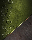 Golden hearts on a green background, with a wooden nameplate — Stock Photo
