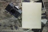 Retro still camera and some old photos on wooden table background — Stock Photo