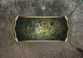 Grunge wall and the black name plate with gold trim — Stock Photo