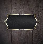 Black nameplate with gold ornate edges, on wooden background — Stock Photo