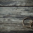 Wedding rings on a dark wooden background. — Stock Photo #38694975