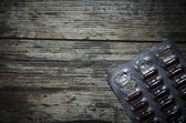 Medical pill on old wooden table. Close up photo — Stock Photo