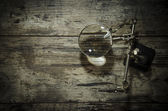 Magnifying glass (magnifying glass) on the old wooden table — Photo