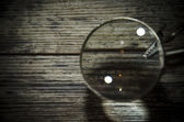 Magnifying glass (magnifying glass) on the old wooden table — Zdjęcie stockowe