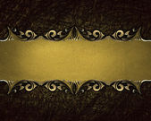 Brown background with a gold plate with decorative borders. — Stock Photo