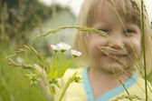 Portrait of a cute little girl smelling a daisy — Stock Photo