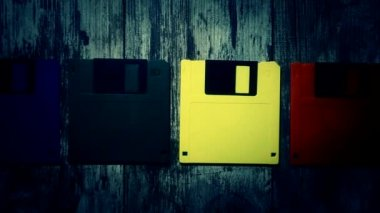 Floppy disks of different colors on a vintage wooden background — Stock Video