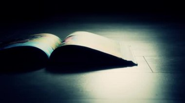 Book in a dark room on the floor — Vídeo Stock
