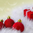 Stock Photo: Red velvet Christmas balls and gift box on white feathers