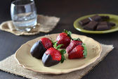 Chocolate strawberries on dark background — Stock Photo