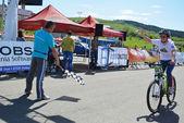 Female bike rider at finish line — Stock Photo