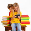 Children - a boy and girl reading e-book surrounded by several books isolate on white background — Stock Photo #21042907