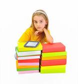 Girl reading e-book among books isolated on white — Stock Photo
