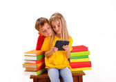Boy and girl looking at e-book surrounded by several books, isolated on white — Stock Photo