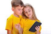 Jungen und Mädchen Blick in die e-Buch — Stockfoto