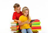 Two children read e-book surrounded by several books isolate on white background — Stock Photo