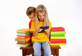 Children - a boy and girl reading e-book surrounded by several books isolate on white background — Stock Photo