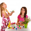 Two girls having fun painting Easter eggs - Stock Photo
