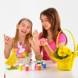 Easter -  Two girls, basket with eggs,  paint for coloring  and a vase of flowers — Stock Photo