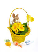 Fluffy bunny basket with yellow flowers and scattered Easter eggs — Stock Photo