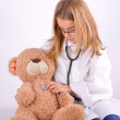 Girl play doctor with her teddy bear — Stock Photo