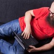 A man on the sofa is resting and working - (Series) - Stock Photo