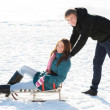 Boy pushing Girl in Sledge — Stock Photo #37777707