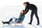 Boy pushing Girl in Sledge — Stock Photo