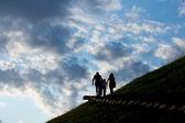 Family walks up the hill — Stock Photo
