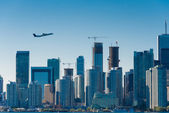 Plane flys over the city — Stock Photo