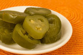 Jalapenos - Bowl of pickled green jalapeno chillies on an orange background. Close up. — Stok fotoğraf