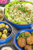 Mezze - Selection of Middle Eastern dishes. Tabbouleh, falafel, olives, sarma, spinach borek, fatayer, hummus and pita bread. — Stock Photo
