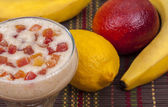 Delicious smoothie of banana, orange, lemon and candied fruit. — Stock Photo