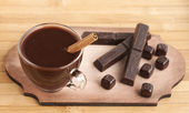 Hot chocolate with cinnamon and spices in a glass cup and chocol — Stock Photo