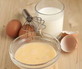 Beat eggs with milk in a glass bowl ,   eggs on a wooden table. — Stock Photo