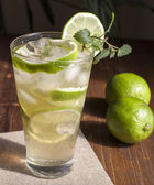 Mojito with fruit lime, mint leaves and ice.  — Stock Photo