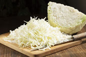 Chopped cabbage strips on a cutting board and a head of cabbage. — Stockfoto
