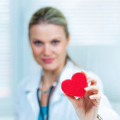Całkiem młoda kobieta lekarz pokazuje czerwone serce w ambulans (płytkiej głębi ostrości, obraz stonowanych kolorów) — Zdjęcie stockowe